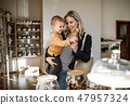 A young woman with a toddler boy buying groceries in zero waste shop. 47957324