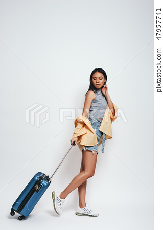 Ready for adventure! Full length of smiling beautiful asian woman carrieng her luggage while 47957741