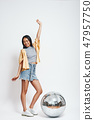 Party girl. Full length portrait of pretty asian woman standing with one raised hand near silver 47957750
