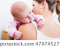Mother carrying her baby sucking pacifier 47974527