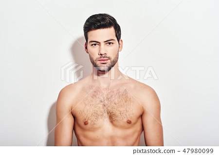 Irresistible man. Handsome man standing shirtless over white background and looking at camera 47980099