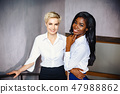 Two beautiful businesswomen are standing together smiling 47988862