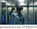 Technician works in a data center wearing a VR headset 47990974