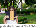 Young cute girl is covering her face with a book. 47991266