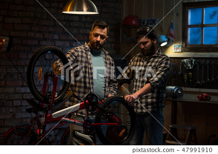 Two men working in a bicycle repair shop 47991910