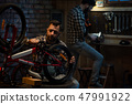 Two men working in a bicycle repair shop 47991922