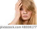 Woman having headache putting hand on head 48008177