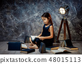 cute little girl is reading a book. 48015113