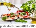 Pouring olive oil on caprese salad.  48015905