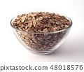 oat flakes in a glass bowl on white backrgound 48018576