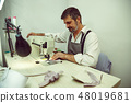 Sewing process of the leather belt. old Man's hands behind sewing. 48019681