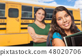 Hispanic Mother and Daughter Near School Bus. 48020706