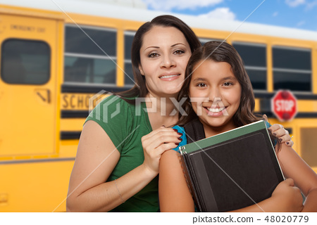 Hispanic Mother and Daughter Near School Bus. 48020779