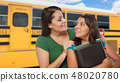 Hispanic Mother and Daughter Near School Bus. 48020780