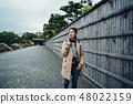 tourist walk along bamboo wall on stone road 48022159