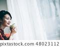 一个红色的单件女士,她的头发坐在靠窗的沙发上 48023112
