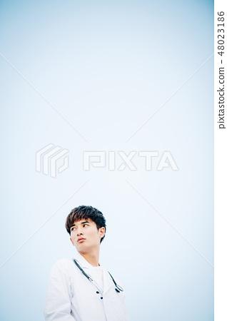 在站立在屋頂的白色外套的男性 48023186