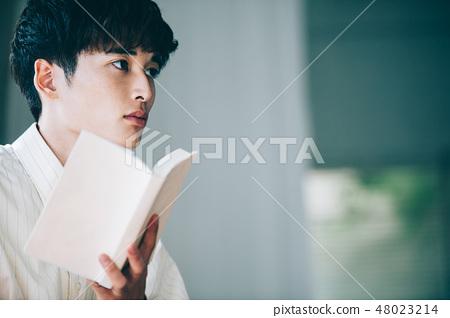 有一件白色襯衣的一個人在窗口旁邊讀書 48023214