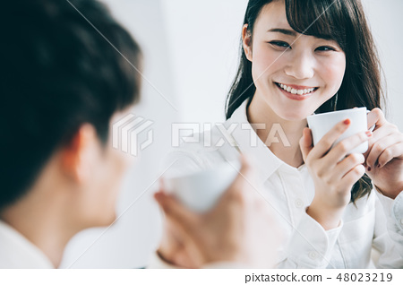 A man and a woman who talks with a mug in a rest room 48023219