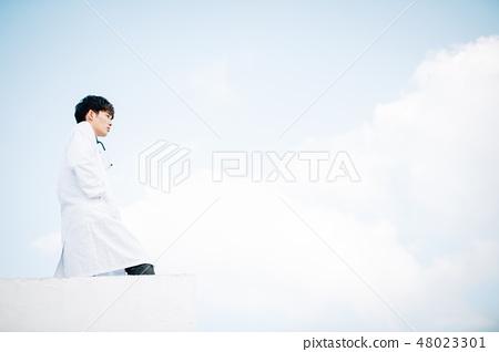 在站立在屋頂的白色外套的男性 48023301