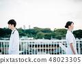 穿白色長袍的男人和婦女站立在屋頂 48023305