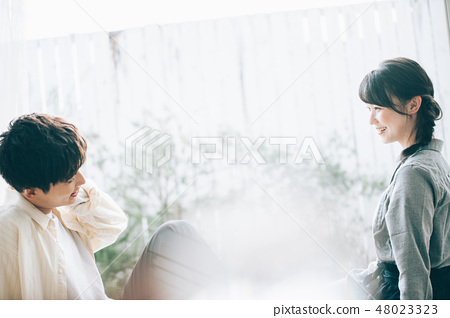 Sitting on a veranda and talking to each other 48023323