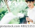 一個在花園裡澆水的男人 48023353