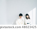 Men and women in white shirt leaning against the wall 48023425