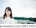 站立在屋頂的一件白色襯衣的一名婦女 48023430