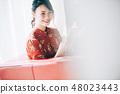 坐在窗户的沙发上,读一本书一个红色的单件女士,她的头发 48023443