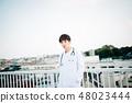 穿在欄杆的一個人一套白色衣服在屋頂 48023444