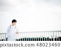 穿在欄杆的一個人一套白色衣服在屋頂 48023460