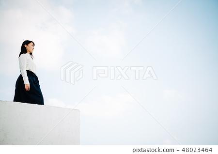 站立在屋頂的一件白色襯衣的一名婦女 48023464