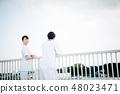 穿在欄杆的男人和婦女白色外套在屋頂 48023471