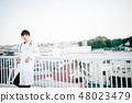 穿在欄杆的一個人一套白色衣服在屋頂 48023479