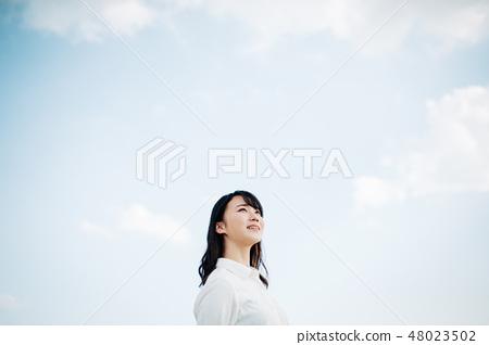 站立在屋頂的一件白色襯衣的一名婦女 48023502
