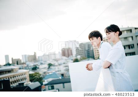 穿著白色長袍的男人和女人在屋頂上排隊 48023513