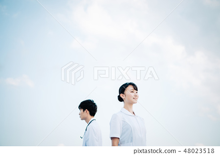 Back-to-back man and woman in a white robe standing on the roof 48023518