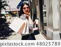 beautiful lady standing on street by cloth shop 48025789