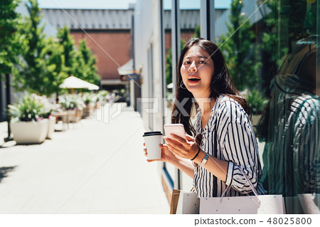 woman standing by fashion store window display 48025800