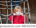 Girl playing on a rope web 48036340