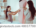 Enthusiastic daughter helping her mother with sewing 48037700