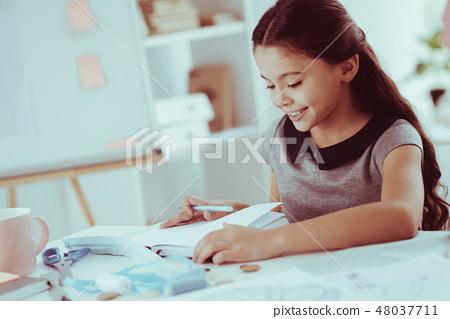 Close up of pleasant girl doing homework 48037711
