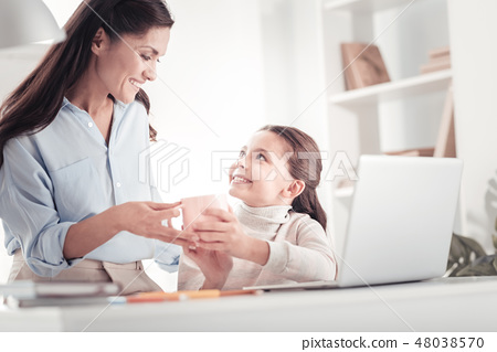 Caring tender mother bringing daughter cup of tea to her child room 48038570