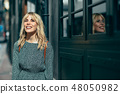 Smiling young blonde woman standing on urban background. 48050982