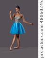 Ballerina wearing blue dress posing in studio 48060245