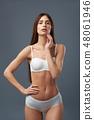Beautiful brunette girl in white lingerie standing against blue-gray background 48061946