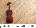 Classic musical instrument. Top view of the brown violin on the wooden floor 48066360