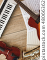 Vertical top view of different musical instruments: synthesizer, guitar, saxophone, violin lying on 48066362