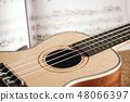 Ukulele chords. Close-up photo of ukulele guitar and music notes against of wooden background 48066397